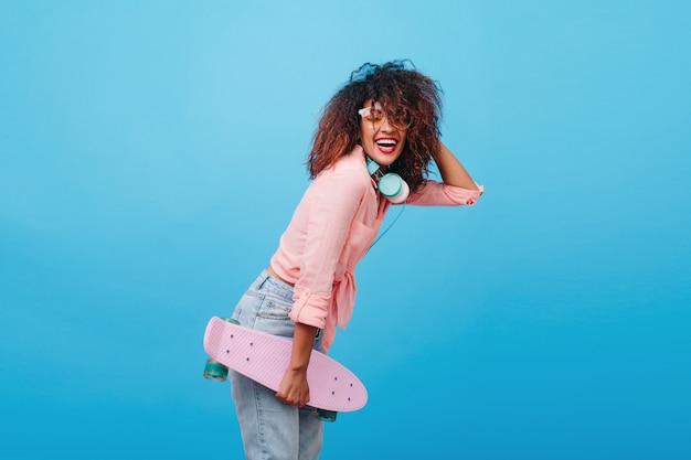スケートボードで笑っている綿のピンクのシャツの魅力的なアフリカの女の子。茶色の髪のスタイリッシュな巻き毛の若い女性は、浮気するヘッドフォンを身に着けています。