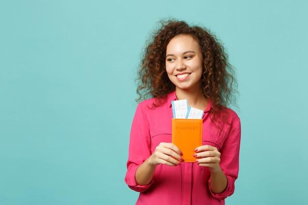 분홍색 캐주얼 옷을 입은 매력적인 아프리카 소녀, 여권을 들고 스튜디오의 파란색 청록색 벽 배경에 격리된 탑승권. 사람들은 진심 어린 감정 라이프 스타일 개념입니다. 복사 공간을 비웃습니다.