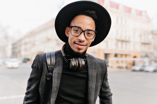 笑顔の暗い目を持つ魅力的なアフリカの男。通りでポーズをとってカジュアルなアクセサリーで黒人の若い男の屋外の肖像画。