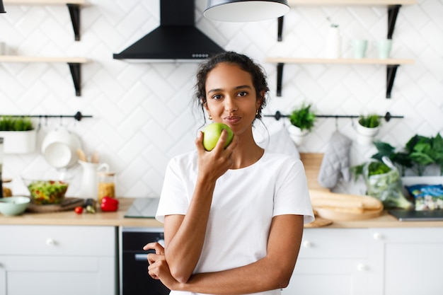 Charming african woman is eating an green apple in the kitchen