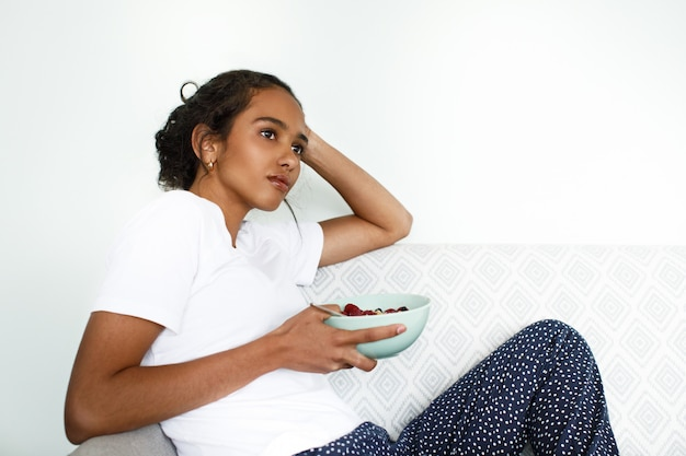 Charming african woman sits on the sofa and holds a bowl with oatmeal