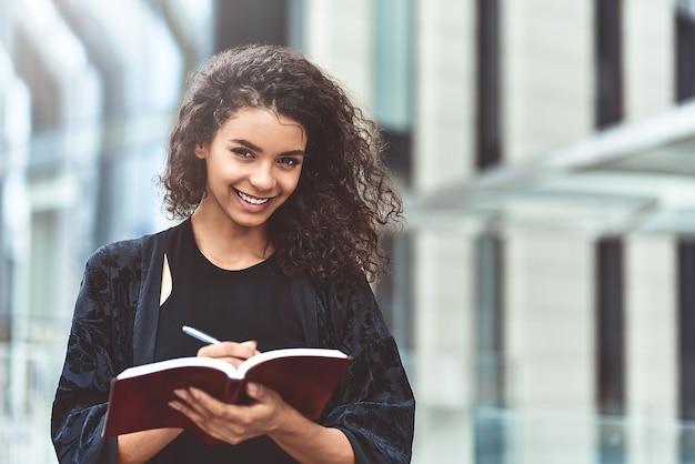 屋外を歩きながらメモ帳でメモを作る魅力的なアフリカ系アメリカ人の美しい幸せな女性
