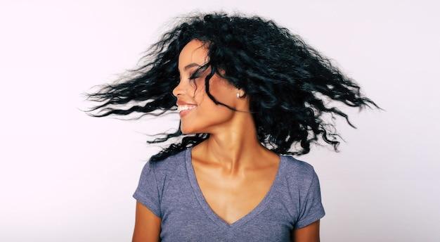 Очаровательная афроамериканка с вьющимися темными волосами хлестает волосы с закрытыми глазами и смеется от радости.