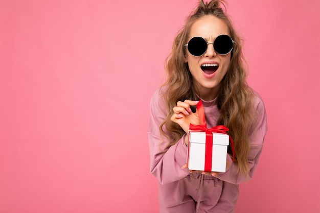 Charming amazed astonished young blonde curly woman isolated over pink background wall wearing pink sport clothes and sunglasses holding gift box looking at camera. copy space