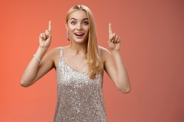 Charming amazed blond european woman in fabulous silver glittering dress raise hands point up amused enjoying watching shooting stars, fireworks gaze camera excited happy surprised, red background.