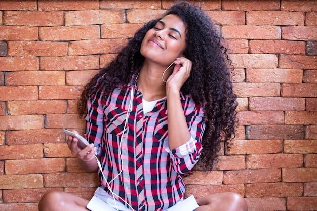 매력적인 놀라운 아프리카 미국 젊은 여성, 그녀의 휴대 전화에 헤드폰에서 음악을 들으면서 춤.