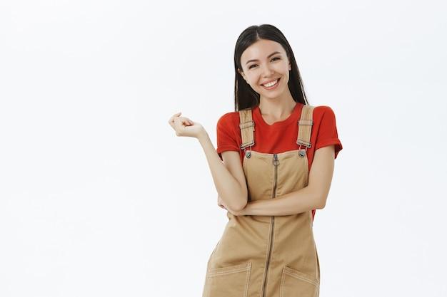 Очаровательная, довольная и счастливая европейка в милом комбинезоне над красной футболкой, склонив голову, радостно смеясь