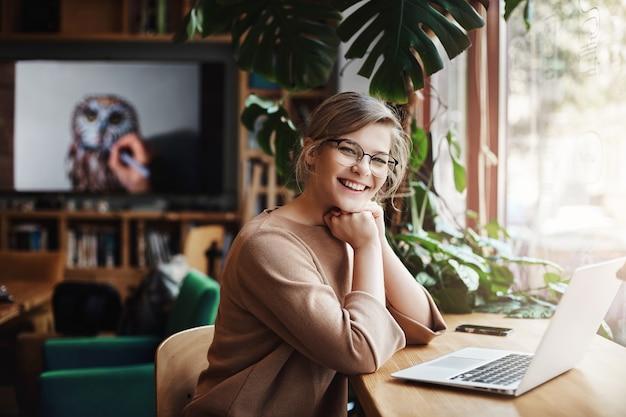 Очаровательная и беззаботная европейская женщина со светлыми волосами в очках, сидя у окна и ноутбука, опираясь на руки.