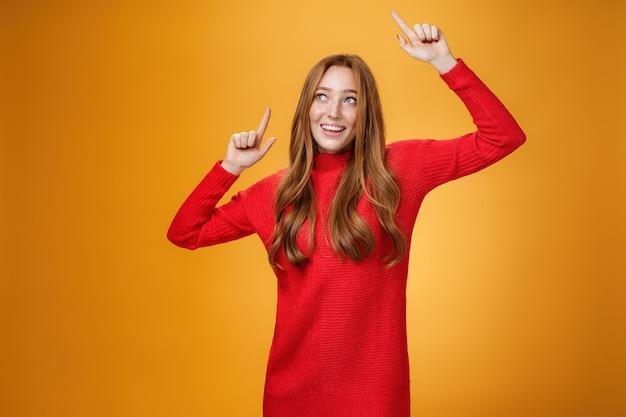 빨간색 니트 드레스를 입은 매력적이고 우아한 매력적인 빨간 머리 여성은 왼쪽 상단 모서리에서 넓은 미소를 지으며 즐겁게 웃고 즐겁게 응시하며 즐겁게 춤을 추며 손을 위로 들어올립니다.