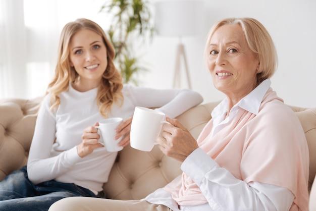 Очаровательная и элегантная старшая женщина сидит на диване рядом со своей дочерью, одновременно держа чашку чая и глядя вперед с улыбкой