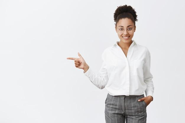 고객에게 방법을 보여주는 매력적이고 친절한 회사원. 안경과 바지에 정중하고 똑똑하고 창의적인 여성 고용주의 초상화, 주머니에 손을 잡고, 왼쪽을 가리키는, 출구에서 표시