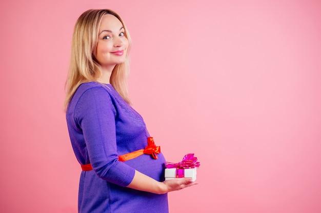 매력적이고 부드러운 금발의 임산부 배 아기 범프는 분홍색 배경의 스튜디오에 있는 드레스에 선물이 든 상자를 들고 있습니다. 베이비 샤워의 개념입니다.