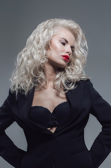 灰色のスタジオで黒いブラとジャケットでポーズをとる魅力的でセクシーなブロンドの女性