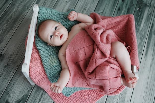 Очаровательный и милый новорожденный накрыт вязанным пледом на деревянной кровати ручной работы на зеленом фоне деревянного паркета.