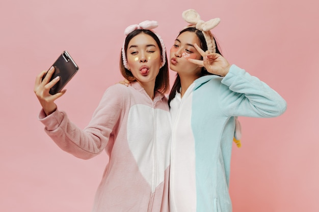 Charming asian brunette women in soft pajamas and headbands make funny faces and take selfie on pink wall