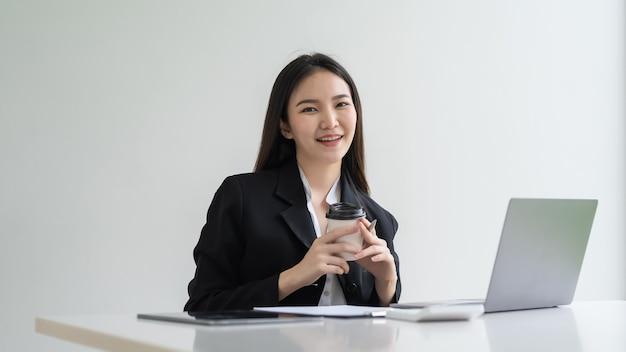 コーヒーカップのラップトップドキュメントを保持しているオフィスに座っている魅力的なアジアの実業家。カメラを見てください。