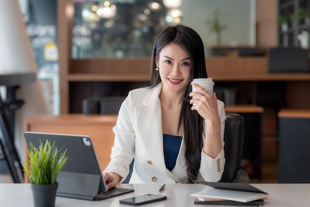 オフィスでタブレットを使用する準備ができてコーヒーを保持しているオフィスで働く魅力的なアジアの実業家。カメラを見てください。