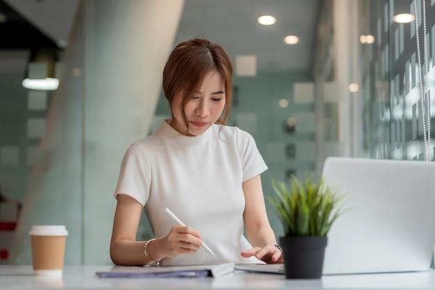 현대 사무실에서 일하는 매력적인 아시아 사업가.