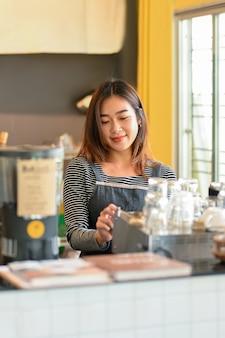 コーヒーショップのコーヒー醸造所でコーヒーマシンでコーヒーを作る魅力的なアジアの女性バリスタ