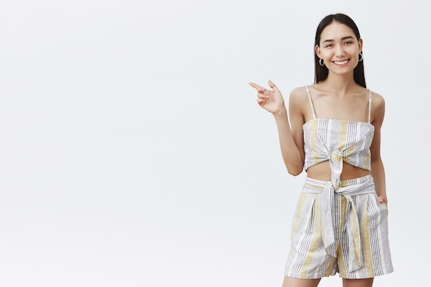 Charming asian female model in matching outfit, holding hand in pocket of shirts and pointing left while smiling joyfully and friendly, showing way to bar, asking brink cocktail