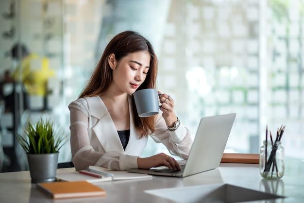 Очаровательная азиатская женщина-офисный работник работает на портативном компьютере и наслаждается пить кофе в современном офисе