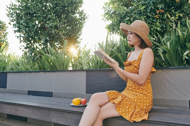 Charming asian girl relaxing in the spring park while read book.