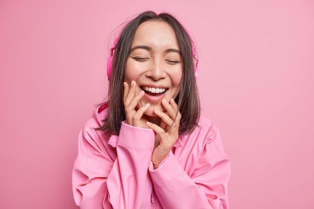 매력적인 아시아 십대 소녀가 얼굴에 손을 대고 킥킥 웃으며 긍정적으로 눈을 감고 스테레오 헤드폰을 통해 좋아하는 음악을 듣고 분홍색 벽 위에 절연 재킷을 입습니다. 행복 한 감정 개념