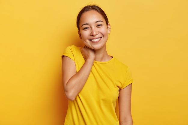 매력적인 아시아 여성은 쾌활한 표정을 지으며 목을 만지고 머리를 기울이고 대담 자와 즐거운 대화를 나누고 즐거운 소식을 듣고 생생한 캐주얼 티셔츠를 입고 노란색 벽에 고립 된