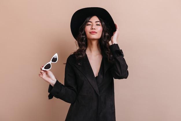 カメラを見て黒いコートを着た魅力的なアジアの女性。ベージュの背景に立っている帽子の美しい日本人女性。