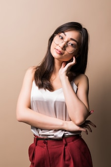 Charming asian woman standing isolated over beige wall