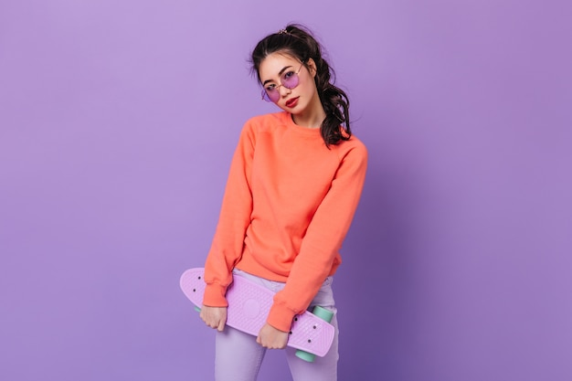 Charming asian woman with ponytail holding skateboard. studio shot of adorable chinese young woman posing on purple background.