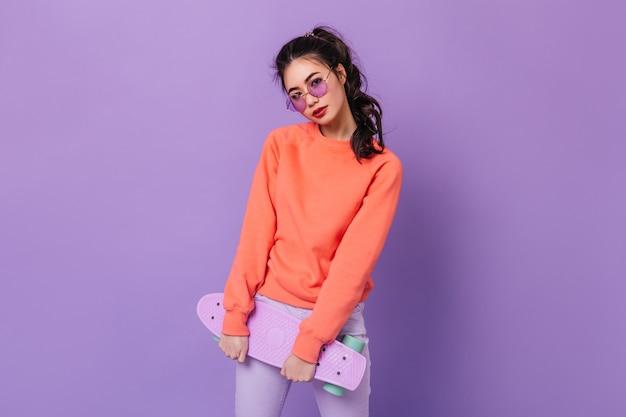 Очаровательная азиатская женщина с хвостиком, держащим скейтборд. студия сняла очаровательную китайскую молодую женщину, позирующую на фиолетовом фоне. Бесплатные Фотографии