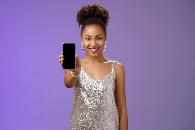 Очаровательная привлекательная афро-американская женщина в серебряном блестящем стильном платье протягивает руку, показывая дисплей смартфона, представляя приложение, продвигающее крутое устройство, стоящее на довольном улыбающемся синем фоне.