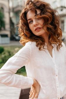 Affascinante attraente donna riccia che indossa una camicia bianca in posa all'esterno con un sorriso durante il servizio fotografico