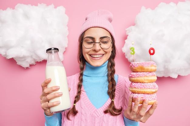 Очаровательная привлекательная девушка улыбается позитивно, скромно празднует свое 30-летие, держит пончики с номерными свечами и бутылку молока, одетую в повседневную одежду, стоит в помещении.