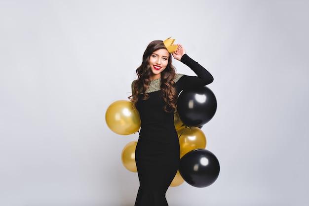 Affascinante donna attraente festeggia il compleanno in abito di lusso nero, con palloncini neri e oro, indossa una corona gialla. divertirsi, festa di capodanno.