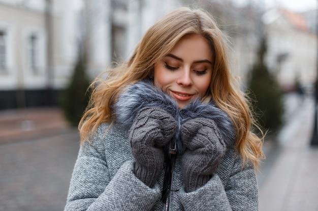 니트 장갑에 세련된 따뜻한 겨울 겉옷에 매력적인 매력적인 젊은 여자 금발은 주말을 즐깁니다. 꽤 유행 소녀.