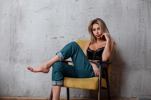 세련된 청바지에 고급스러운 블랙 레이스 보루에 자연스러운 메이크업으로 금발 긴 머리를 가진 매력적인 매력적인 젊은 여자가 빈티지 의자에 포즈