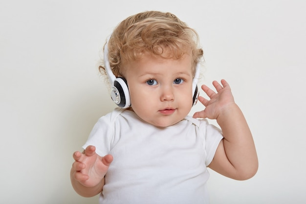 Charming baby boy with beautiful eyes posing with headphones, listening to music, isolated on white space