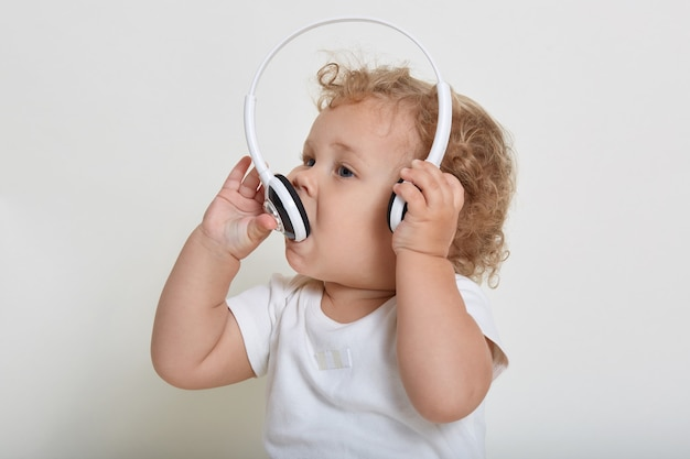 Charming baby boy with blond hair playing with headphones