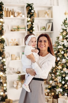 Charming baby girl and her beautiful happy mother standing against decorations