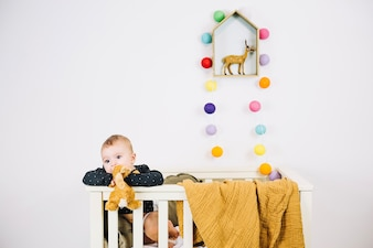 Charming baby in cradle chewing toy