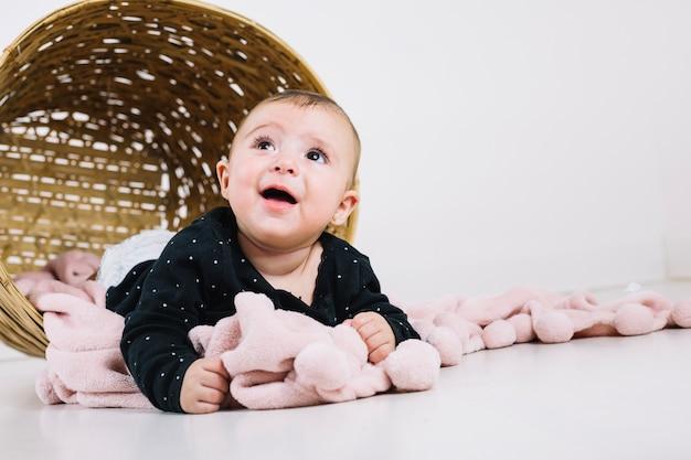Очаровательный ребенок на одеялах возле корзины
