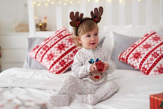 침대에서 크리스마스 선물을 여는 매력적인 아기