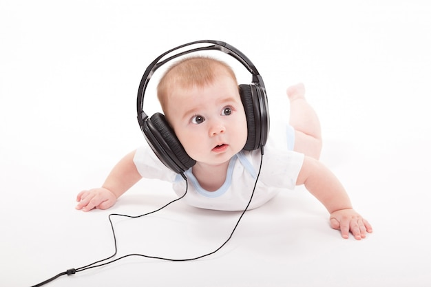 Charming baby on a white background with headphones listening to
