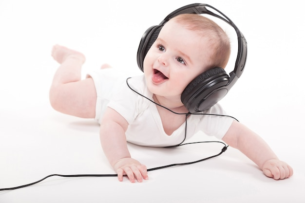 Charming baby on a white background with headphones