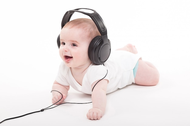 Charming baby with headphones listening music