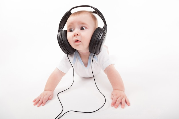 Charming baby with headphones listening