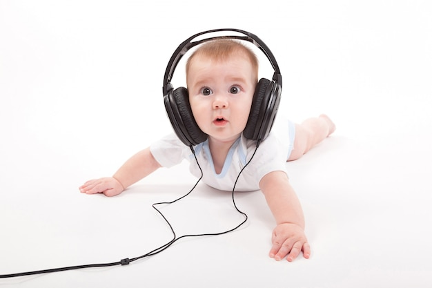 Charming baby with headphones listening to