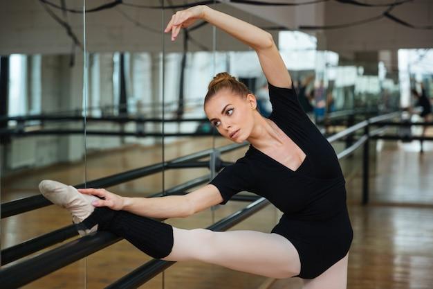 バレエ クラスでストレッチ体操をする魅力的なバレリーナ